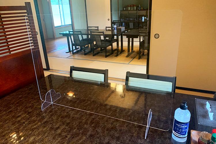各テーブルにパーテーション、消毒液を設置
